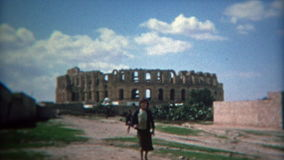 TUNIS, TUNISIA 1972: Kids playing Roman like Collosuem background with blue skies. Unique vintage 8mm film home movie professionally cleaned and captured in 4k stock footage