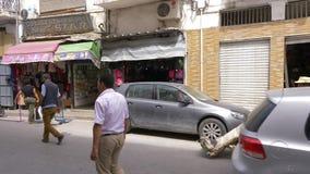Tunisi, Tunisia - 6 giugno 2018: Carriola araba di rotolamento dell'uomo sulla via lungo il negozio della città Gente turistica c archivi video
