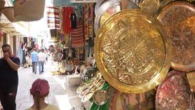 Tunisi, Tunisia - 6 giugno 2018: Ricordi ed utensili arabi del mercato dall'ottone dell'oro Turisti che camminano nel mercato loc stock footage