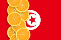 Tunisia flag and citrus fruit slices vertical row. Tunisia flag and vertical row of orange citrus fruit slices. Concept of growing as well as import and export royalty free stock photos