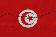 Tunisia flag on concrete wall with crack. Patriotic grunge background. National flag of Tunisia stock photos