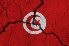 Tunisia flag on the cracked earth. National flag of Tunisia. Earthquake or drought concept stock images