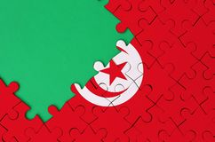 Tunisia flag is depicted on a completed jigsaw puzzle with free green copy space on the left side.  royalty free stock photo