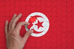 Tunisia flag is depicted on a puzzle, which the man`s hand completes to fold.  royalty free stock photography