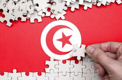 Tunisia flag is depicted on a table on which the human hand folds a puzzle of white color.  stock photo