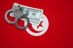 Tunisia flag with handcuffs and a bundle of dollars. The concept of breaking the law and thieves crimes stock image