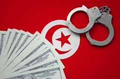 Tunisia flag with handcuffs and a bundle of dollars. The concept of illegal banking operations in US currency.  stock photography