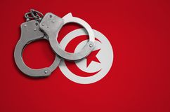 Tunisia flag and police handcuffs. The concept of crime and offenses in the country.  royalty free stock photography