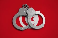 Tunisia flag and police handcuffs. The concept of observance of the law in the country and protection from crime.  stock photography