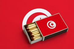 Tunisia flag is shown in an open matchbox, which is filled with matches and lies on a large flag.  stock image