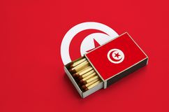 Tunisia flag is shown in an open matchbox, which is filled with matches and lies on a large flag.  royalty free stock photos