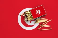 Tunisia flag is shown on an open matchbox, from which several matches fall and lies on a large flag.  royalty free stock image