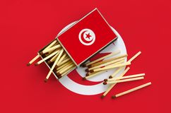 Tunisia flag is shown on an open matchbox, from which several matches fall and lies on a large flag.  royalty free stock photo