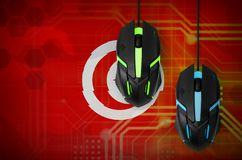 Tunisia flag and two mice with backlight. Online cooperative games. Cyber sport team. Tunisia flag and two modern computer mice with backlight. The concept of royalty free stock photo
