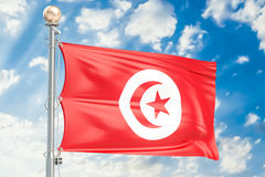 Tunisia flag waving in blue cloudy sky, 3D rendering Royalty Free Stock Images