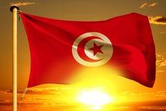 Tunisia flag weaving on the beautiful orange sunset with clouds background. Tunisia flag weaving on the beautiful orange sunset background royalty free stock image
