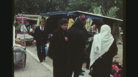 Second Hand Clothes Open Air Market. TUNISIA, MATMATA REGION, WINTER 1973. Three Shot Sequence With Pan. Group Of Men Standing Around And Searching In A Pile Of stock footage