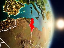 Tunisia during sunrise. Highlighted in red on planet Earth with visible country borders. 3D illustration. Elements of this image furnished by NASA Royalty Free Stock Photos