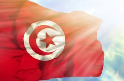 Tunisia waving flag against blue sky with sunrays stock photography