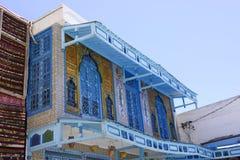 Tunisian Blue Window Shutters and Balcony, Traditional Arabic Art. Tradicional tunisian white building with beautiful blue window shutters, El Jem, Tunisia Royalty Free Stock Photo