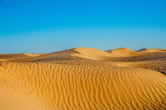 Tunisian desert landscape with blue sky. Dunes background. Royalty Free Stock Images