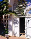 Entrance to Tunisian public house. White doors on wall outside public house in Tunisia stock photography