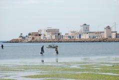 Tunisian fishermens in flowering green sea Stock Photo