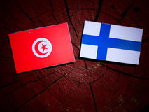 Tunisian flag with Finnish flag on a tree stump isolated. Tunisian flag with Finnish flag on a tree stump stock photography