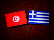 Tunisian flag with Greek flag on a tree stump isolated. Tunisian flag with Greek flag on a tree stump stock photography