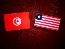 Tunisian flag with Liberian flag on a tree stump isolated. Tunisian flag with Liberian flag on a tree stump stock images
