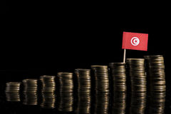Tunisian flag with lot of coins on black. Background stock photography