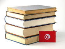 Tunisian flag with pile of books on white background. Tunisian flag with pile of books on white stock photo