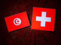 Tunisian flag with Swiss flag on a tree stump isolated. Tunisian flag with Swiss flag on a tree stump royalty free stock photos
