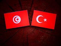 Tunisian flag with Turkish flag on a tree stump royalty free stock photography