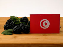 Tunisian flag on a wooden panel with blackberries isolated on a. White background royalty free stock photography