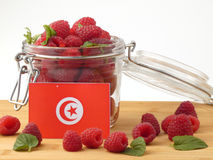 Tunisian flag on a wooden panel with raspberries isolated on a w. Hite background stock image