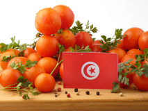 Tunisian flag on a wooden panel with tomatoes isolated on a whit. E background royalty free stock image