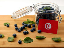 Tunisian flag on a wooden plank with blueberries on whi. Te stock image