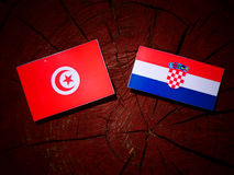 Tunisisk flagga med den kroatiska flaggan på en isolerad trädstubbe Royaltyfri Foto