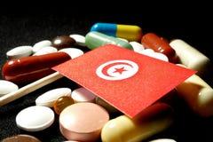Tunisisk flagga med lotten av medicinska preventivpillerar som isoleras på svart backgr Arkivbild