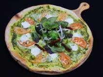 Tunn skorpapizza med den basilikapesto och tomaten, också som är bekanta som lagarapizza royaltyfri bild