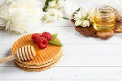 Tunna belgiska dillandear med honung och hallon Jasminblommor och en krus av honung på en ljus träbakgrund Arkivbilder
