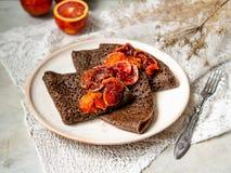 Tunna chokladpannkakor med blodapelsinsås på en vit platta på grå bakgrund med snör åt tyg Bunt av kräppar, ryss royaltyfri foto