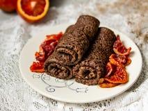 Tunna chokladpannkakor rullade in i ett rör med blodapelsinsås på en vit platta Bunt av kräppar, ryssblin, Maslenitsa royaltyfri bild