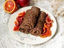 Tunna chokladpannkakor rullade in i ett rör med blodapelsinsås på en vit platta Bunt av kräppar, ryssblin, Maslenitsa arkivbilder