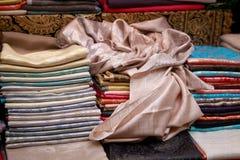Tunna härliga handgjorda pashminasjalar ligger på räknaren royaltyfria foton