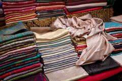 Tunna härliga handgjorda pashminasjalar ligger på räknaren royaltyfri bild