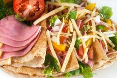 Tunna pannkakor med skinka, ost och grönsaker Royaltyfri Bild