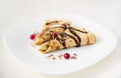 Tunna pannkakor vikt triangel med bär och chokladsås på en vit platta, vit bakgrund Royaltyfri Foto