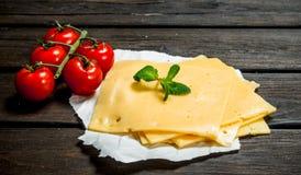 Tunna skivor av ost med tomater och en filial av mintkaramellen royaltyfri fotografi